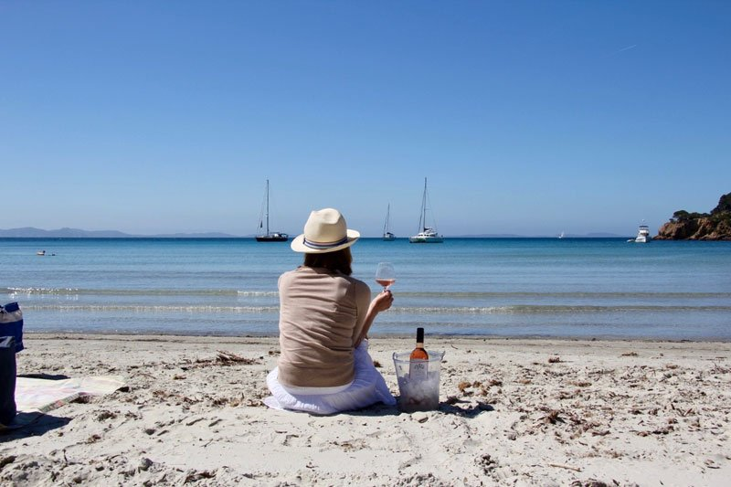 Woman drinking a glass of wine while sitting on a beach